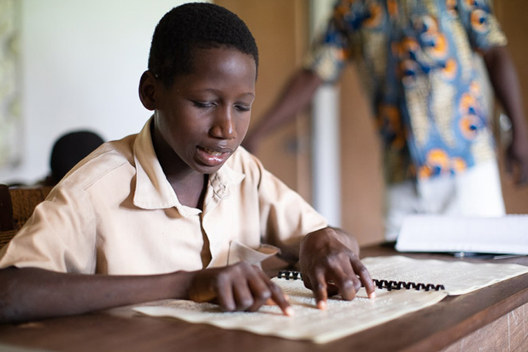 ANNANI READS FROM HIS BRAILLE TEXTBOOK DURING MORNING CLASSES AT THE VILLAGE OF LIGHT SCHOOL FOR THE BLIND.