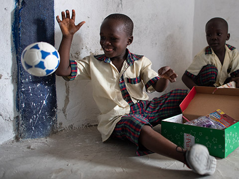 Boy plays with football from shoebox
