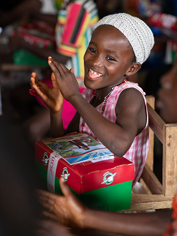 Girl claps and celebrates receiving shoebox gift