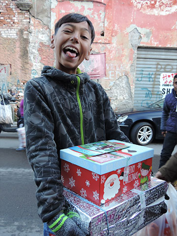 Boy with cheeky grin and shoebox gifts
