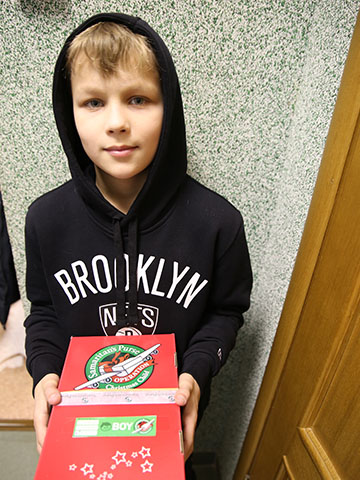 Boy in hood with shoebox gift