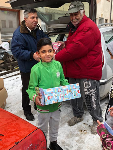 Boy holding shoebox gift in snow