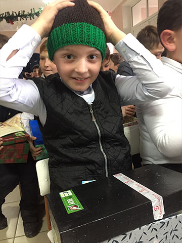 Boy tries on hat from shoebox