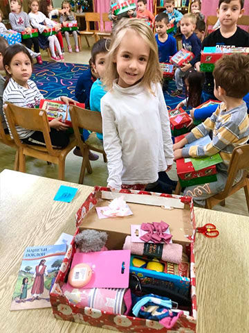 Girl proudly shows shoebox gift