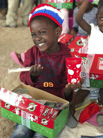 girl smiles at shoebox gift contents