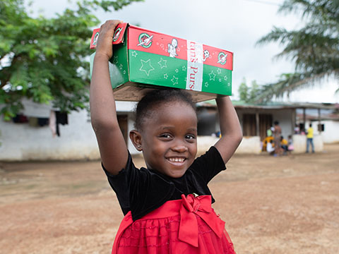 Little girl holds shoebox on head