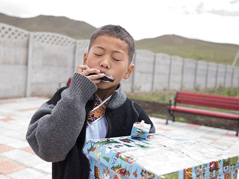boy plays harmonica