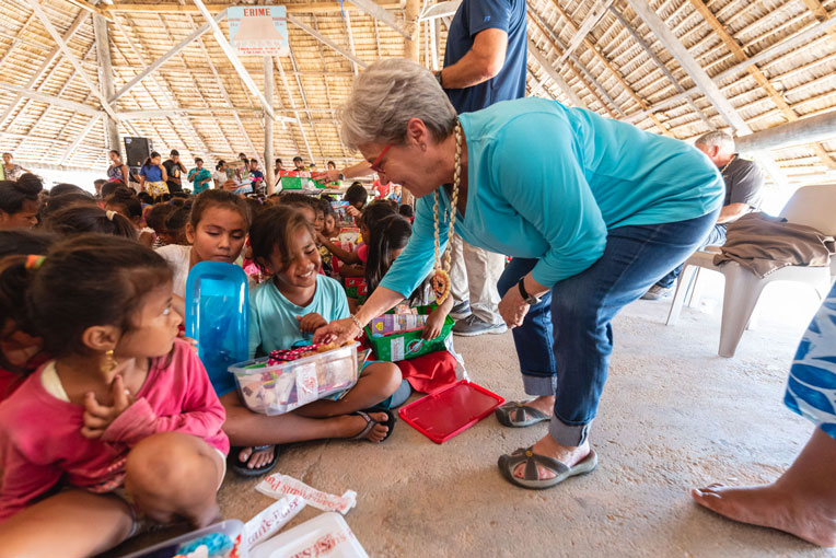 JANE GRAHAM DELIVERS GIFTS AS WELL DURING AN OUTREACH EVENT IN THE PACIFIC ISLANDS.