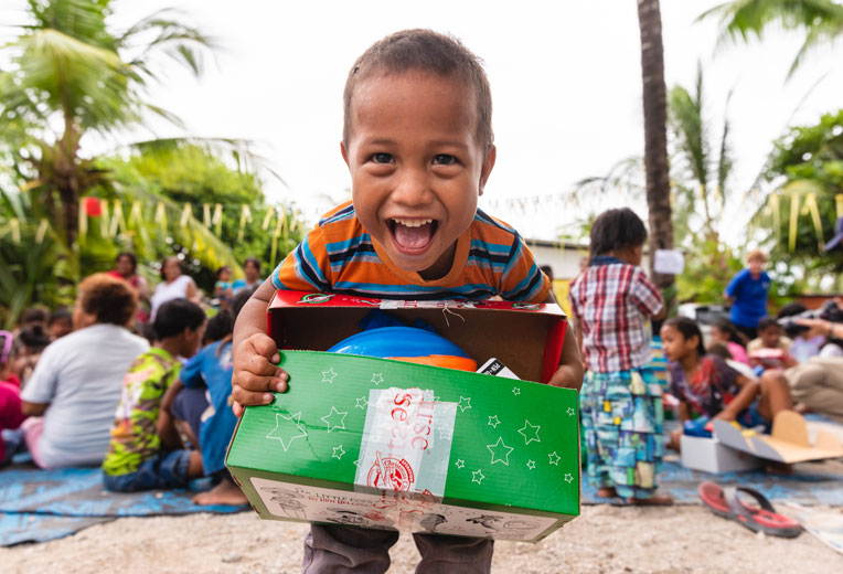 A CHILD EXCITEDLY SHOWS OFF HIS SHOEBOX AFTER RECEIVING THE SPECIAL GIFT DURING AN OUTREACH EVENT IN HIS VILLAGE.