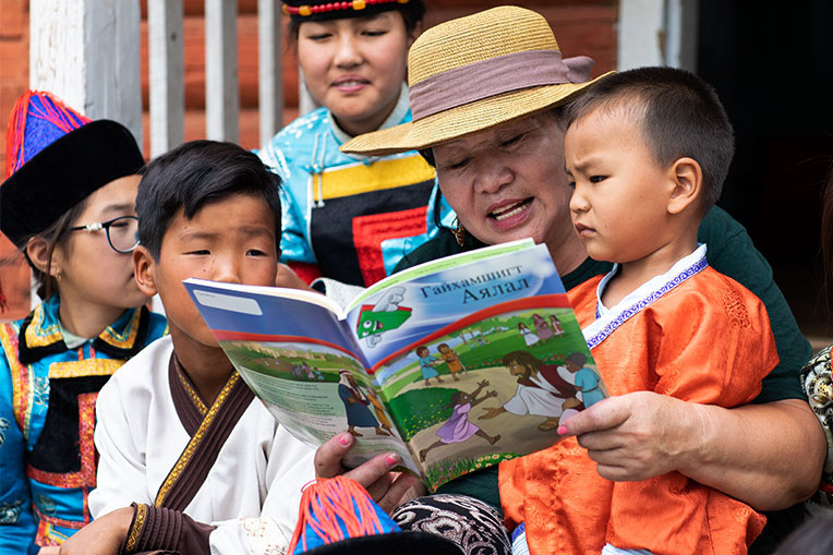 TUYA SHARES THE GOSPEL WITH CHILDREN OF THE UNREACHED BURYAT PEOPLE GROUP USING THE GREATEST JOURNEY WORKBOOK.