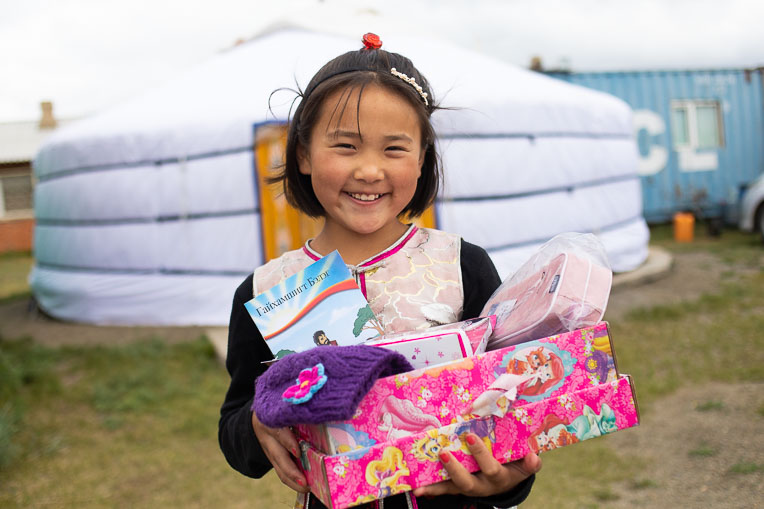 A YOUNG GIRL IN MONGOLIA SHOWS OFF THE TREASURES SHE RECEIVED IN HER SHOEBOX AND THE GOSPEL STORYBOOK IN HER LANGUAGE SHE WAS GIVEN ALONGSIDE IT.