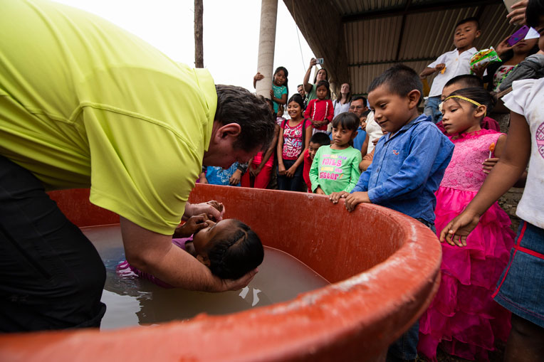 CHILDREN GATHER AS ONE OF THEIR FRIENDS IS BAPTIZED BY A PASTOR OF THE NEWLY DEDICATED CHURCH.