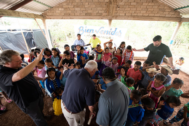CHILDREN, CHURCH LEADERS, EDWARD GRAHAM, AND OTHERS GATHER TOGETHER AS JIM HARRELSON (CENTER IN BLUE SHIRT) LEADS IN PRAYER DURING THE CHURCH DEDICATION.