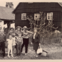 A group of people standing outside a house in Srbska