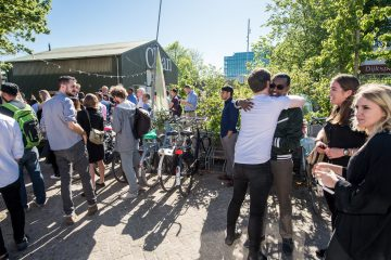 Two men are hugging each other outside at the 2017 TFF Bootcamp, the sun is shining. There are more people standing near them.