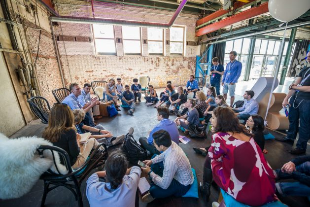 TFF Academy participants sitting in a circle on the floor, discussing food & ag innovations, three men are standing at the back.