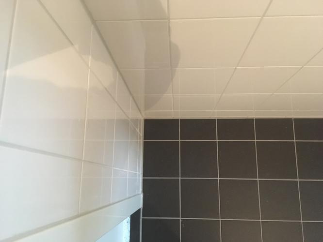 Gat boren door reeds betegelde badkamer betonnen vloer afvoer en