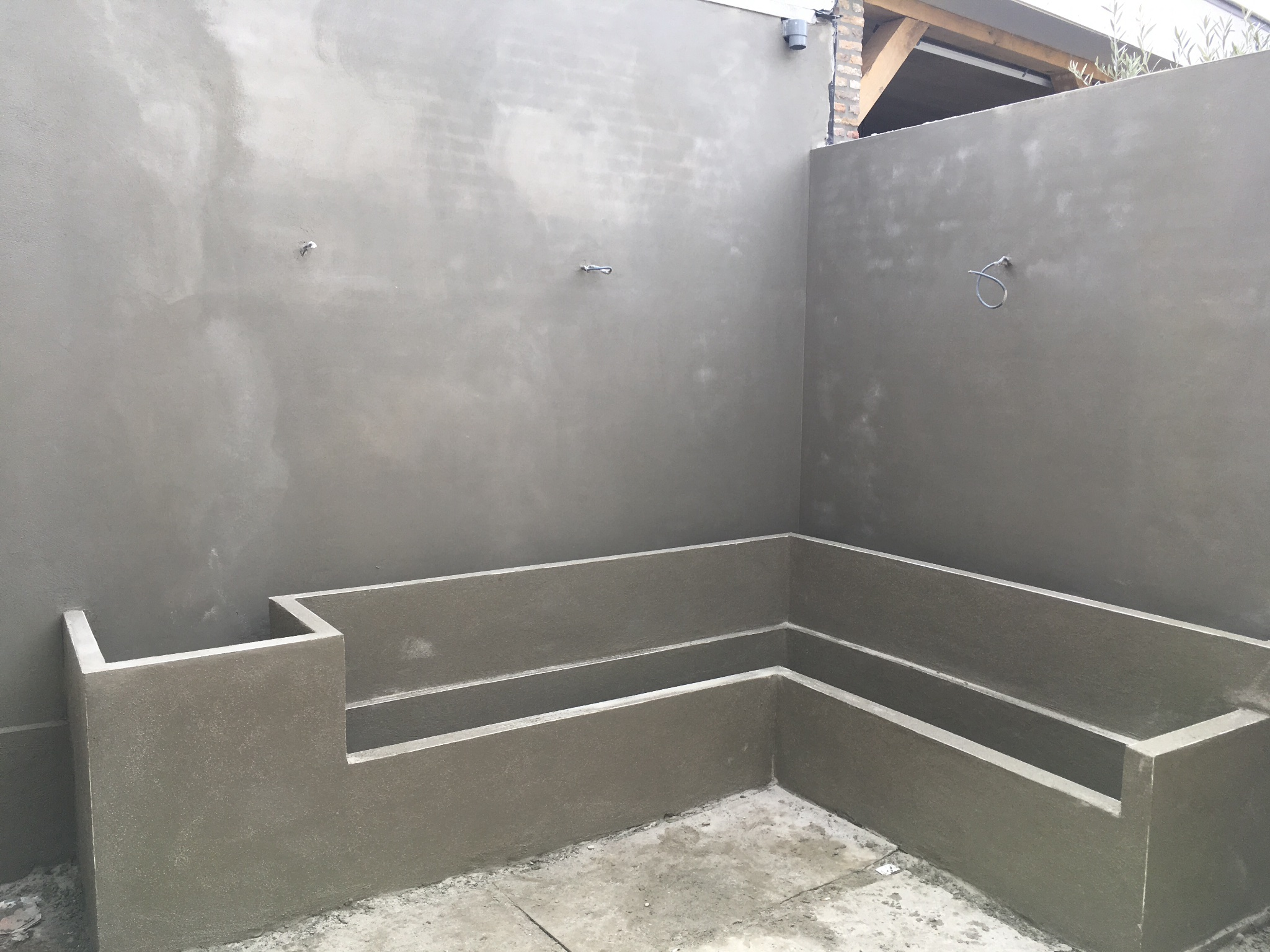 Stucen van twee buitenmuren en een bankje werkspot