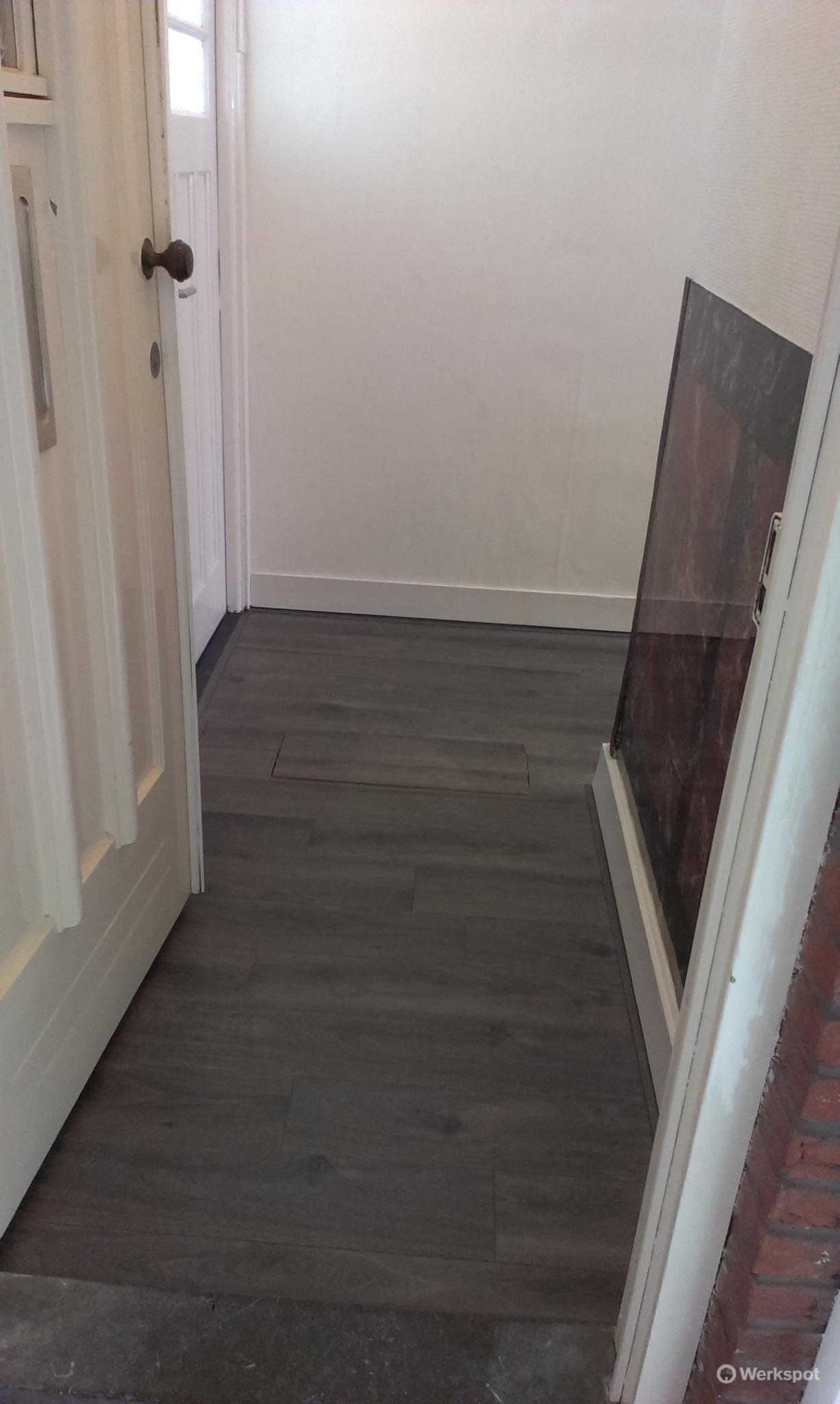 laminaat en vloerplaten leggen in de gang op een houtenvloer