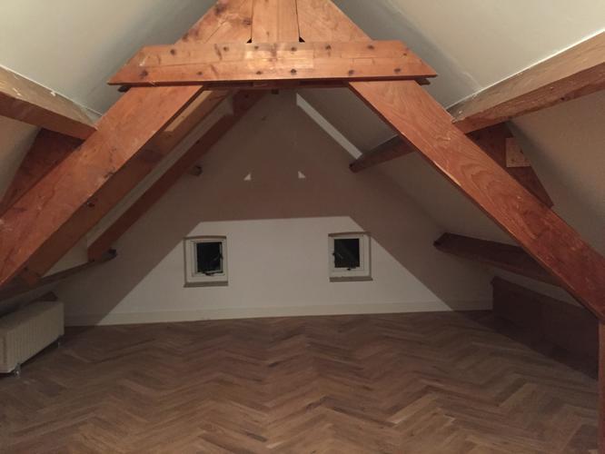Wit schilderen van houten balken op zolder verdieping werkspot