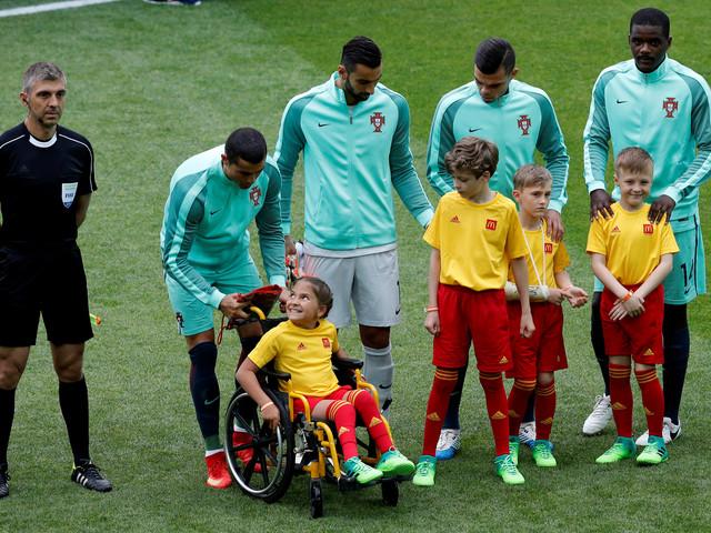 Cristiano Ronaldo entra em campo com menina cadeirante e a presenteia com casaco