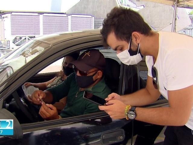Voluntários ajudam profissionais de saúde que trabalham na vacinação contra Covid-19 no Recife