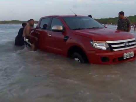 Maré sobe demais e moradores tentam salvar caminhonete de turista