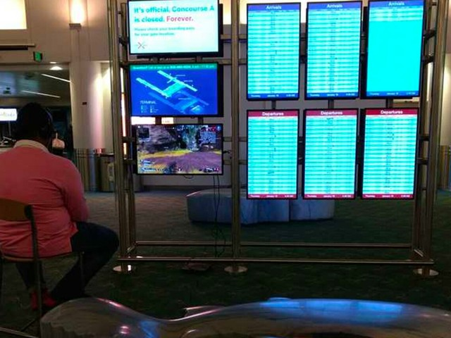 Passageiro usa tela do aeroporto para jogar videogame antes do voo