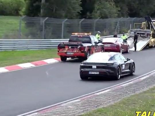 Une Porsche Taycan passe devant une Tesla en panne sur la Nordschleife