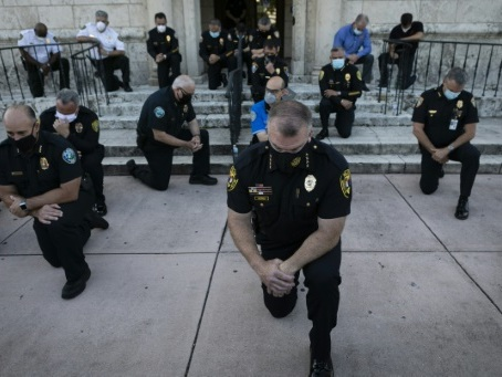 Genou à terre, le signe de solidarité des policiers américains face aux manifestants
