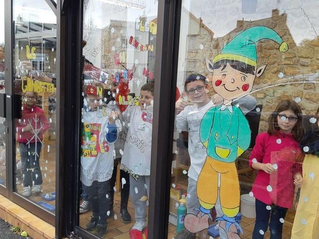 Des enfants décorent les vitrines de Noël d'un établissement blancois