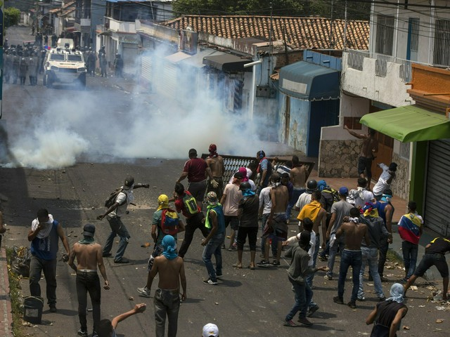 Maduro's opponents brave tear gas in push to deliver aid