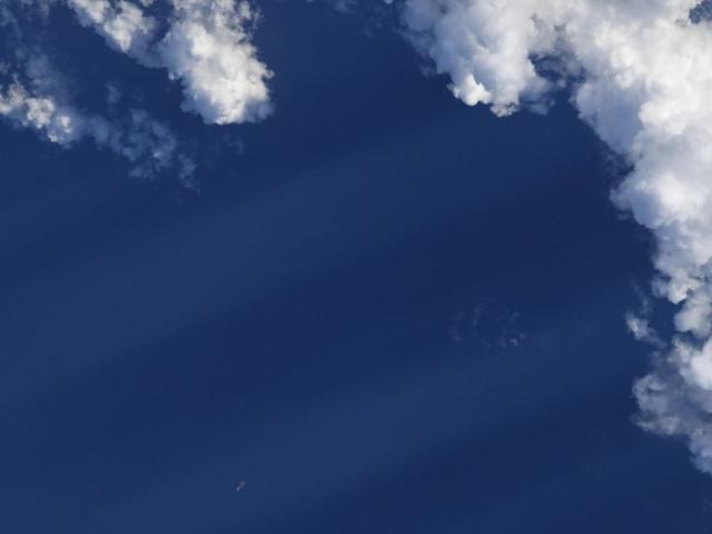 Astronauta della NASA pubblica una foto del cielo con soffici nuvole e chiede di cercare un oggetto creato dall'uomo (FOTO)