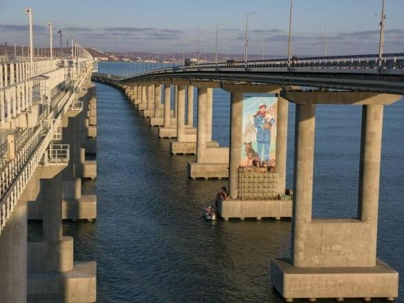 Appare il disegno di un operaio con un gatto tra due piloni del Ponte di Crimea