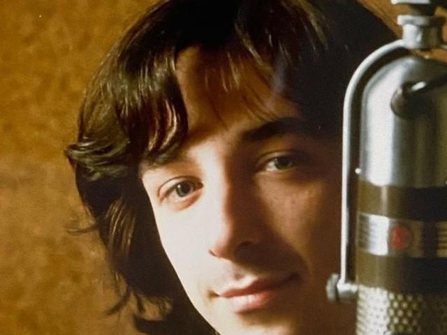 """""""Ma sei tu?"""". Giovanissimo e con i capelli lunghi, riconoscere in questa vecchia foto il super vip italiano è davvero impossibile"""