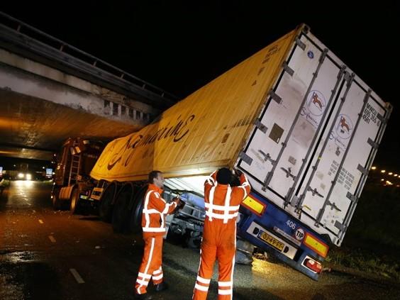 Vrachtwagen rijdt zich klem onder viaduct in Hank