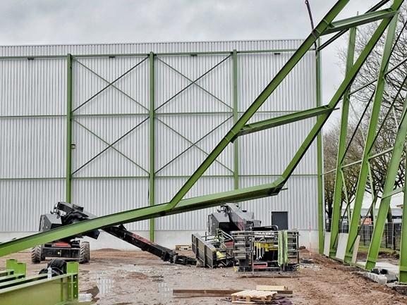 Gewonde bij ongeluk met stalen frame op bouwplaats, vallende constructie raakt hoogwerker