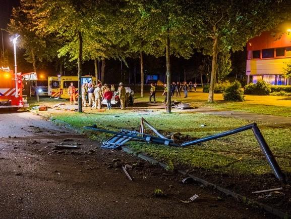 Auto ramt lantaarnpaal en slaat drie keer over kop, bestuurder bekneld