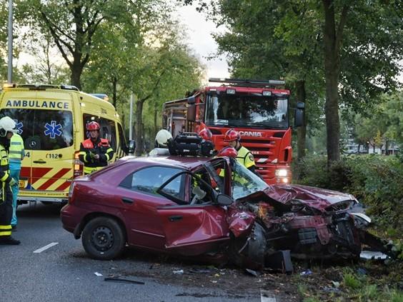 Auto tegen boom, bestuurder met spoed naar ziekenhuis