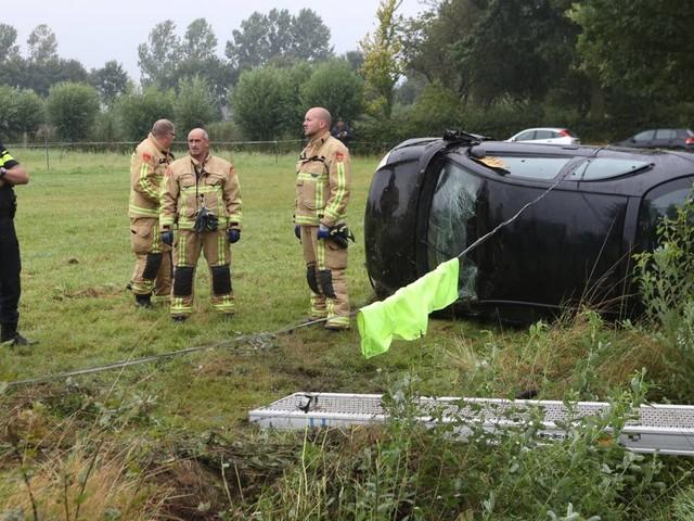Auto met vrouw en kind raakt van de weg en belandt op kant in weiland