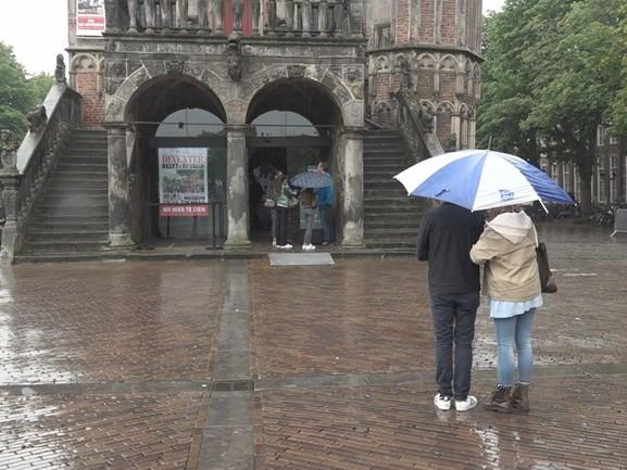 Toeristen in Overijssel gaan in de regen op zoek naar vertier in de stad