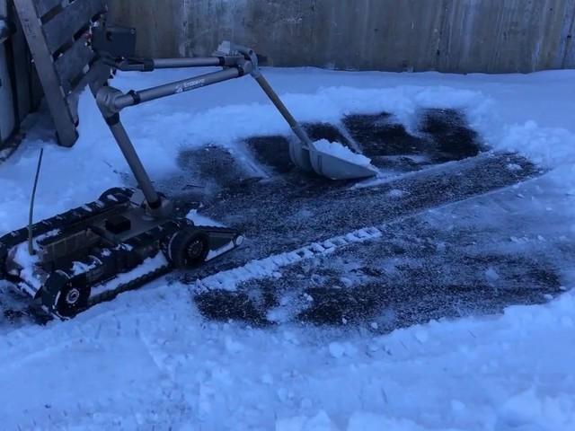 Roboten PackBot skottar snö