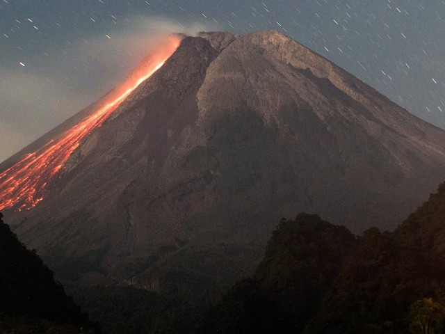 Mount Merapi erupts spewing hot ash and gas into the air as lava oozes down its slopes