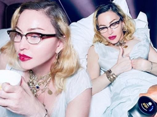 Madonna looks glamorous in a plunging ivory satin gown as she has a cup of tea in bed