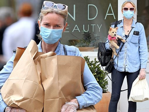 Naomi Watts wears a face mask and plastic gloves with rescue dog in New York