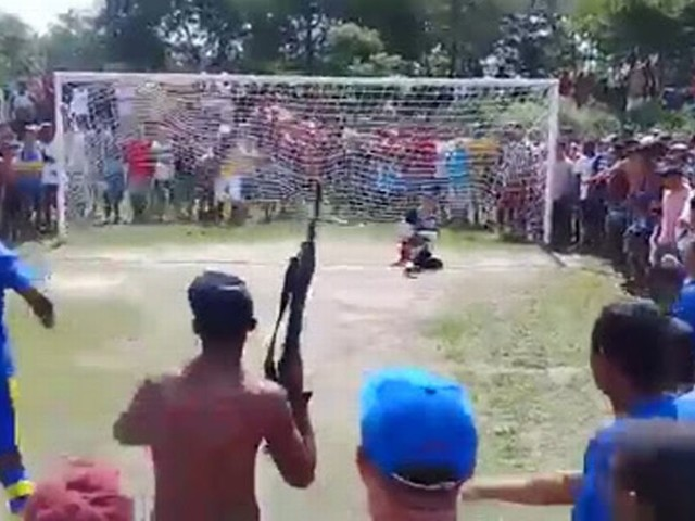 Imagine if he missed?! Footballer holds his nerve to convert penalty in front of machine gun-toting fans