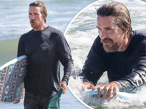 Christian Bale sports a bristly beard as he takes to the water for another morning surfing session