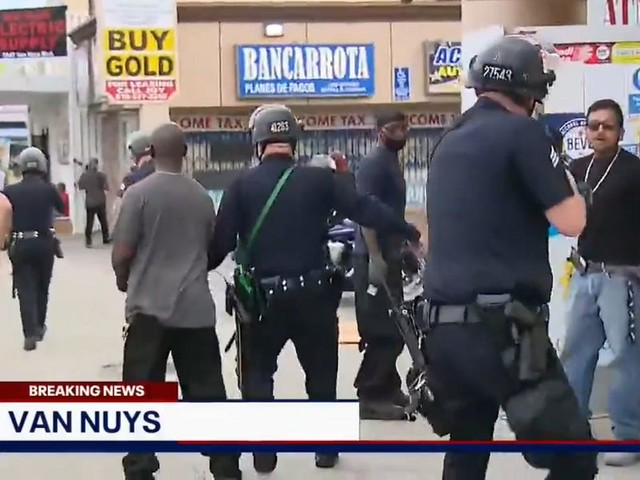 Los Angeles police detain group defending store on live television, while would-be burglars flee
