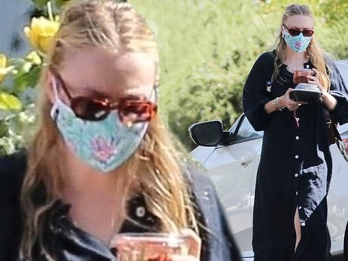 Dakota Fanning cuts a casual figure in a loose-fitting black dress as she carries an armful of food