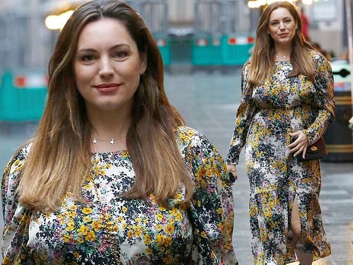 Kelly Brook shrugs off the rain in a vibrant floral print summer dress